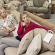 Mother and daughter sitting on sofa while looking at price tag in furniture store — Stock Photo #21880837