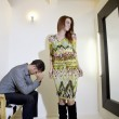 Young woman looking at self in mirror while man sitting on chair with hands on face — Stock Photo #21882375