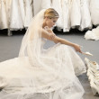 Side view of young woman in wedding dress confused while selecting footwear — Stock Photo #21883537