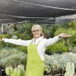 Portrait of a senior woman standing with arms outstretched in garden center - Stock Photo
