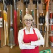 Portrait of a happy senior woman with arms crossed in front of gardening tool — Stock Photo