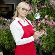 Portrait of a senior florist making notes in garden center — Stock Photo
