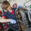 Young female mechanic working with welding torch on vehicle machinery part in auto repair shop — Stock Photo #21880283