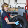 Portrait of a confident young female mechanic carrying tire in vehicle repair shop - Stock Photo