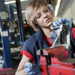 Young female mechanic in protective workwear working on machinery part in automobile repair shop — Photo