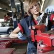 Stock Photo: Young mechanic in protective clothing concentrating on repairing machine part in garage