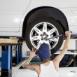 Back view of young female working on car tire in workshop — Стоковое фото