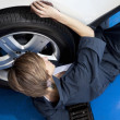 High angle view of young mechanic lying on floor working on car tire in garage — Stock Photo