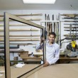 Portrait of a happy young man working on big picture frame in workshop — Stock Photo