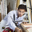 Portrait of a confident craftsman working on picture frame — Stock Photo