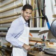 Portrait of a happy young craftsman standing by circular saw machinery — Stock Photo