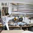 Back view of young man using circular saw in workshop — Stock Photo