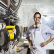 Foto Stock: Portrait of skilled worker standing with hands on hips in workshop