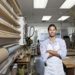 Stock Photo: Portrait of happy skilled worker standing with arms crossed in workshop