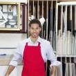 Stockfoto: Portrait of happy young skilled worker standing with meter stick in workshop