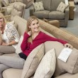 Portrait of happy mother and daughter sitting on sofa in furniture store — ストック写真