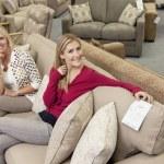 Retrato de la feliz madre e hija sentada en el sofá en la tienda de muebles — Foto de Stock
