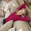 Portrait of daughter relaxing on sofa while mother looking in furniture store — Stock Photo