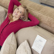 Portrait of a happy young woman with hands behind head relaxing on sofa in furniture store — ストック写真
