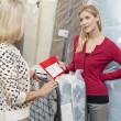 Young woman holding price list while looking at mother in furniture store — Stock Photo #21880949