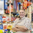 Portrait of a happy mature salesperson with arms crossed in hardware store - Stock Photo