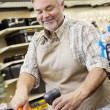 Stock Photo: Happy mature store clerk using barcode reader at checkout counter