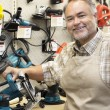 Stock Photo: Portrait of happy salesperson with electric saw in hardware store