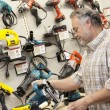 Stock Photo: Side view of mature salesperson looking at electric saw