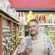 Stock Photo: Mature salesperson reading something in hardware store