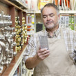 Mature salesperson reading instructions in hardware store - Stock Photo