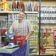 Portrait of a mature man with shopping cart in hardware store — Stock Photo #21881097