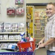 Side view portrait of a happy mature man with shopping cart in hardware store — Stock Photo #21881111