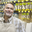 Happy mature salesperson in hardware store looking away - Stok fotoğraf