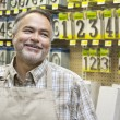 Stock Photo: Happy mature salesperson in hardware store looking away