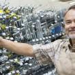 Portrait of a happy mature salesperson holding metallic equipment in hardware store — Stock Photo