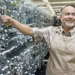 Happy mature salesperson holding metallic equipment while looking away in hardware store — Stock Photo #21881151