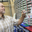 Happy mature man looking at staple pack in store — Stock Photo