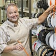 Portrait of a happy mature store clerk with electrical wire spool in hardware shop — Stock Photo #21881165