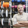 Portrait of a happy mature salesperson standing in front of electrical wire spool with arms crossed in hardware store — Stock Photo #21881195