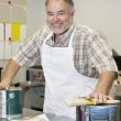 Portrait of a cheerful mature store clerk with paint cans and brush in hardware shop — Stock Photo
