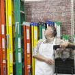Mature salesperson standing by multicolored ladders in hardware store — Stock Photo #21881217