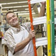 Portrait of a happy mature man with ladder in hardware store - Stock Photo