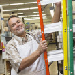 Portrait of a happy mature man with ladder in hardware store — Stock Photo