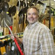 Portrait of happy mature mholding shovel in hardware store — Stockfoto #21881239