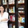 Stock Photo: Portrait of beauty salon employee standing with arms crossed and cosmetics in background
