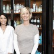 Portrait of beautiful owner with employee standing in front of cosmetic products — Stock Photo