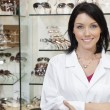 Portrait of a beautiful optometrist with arms crossed in store — Stock Photo