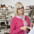 Optician holding mirror while senior female customer looking — Stock Photo