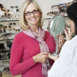 Portrait of senior woman wearing glasses while optician holding mirror - Stock Photo
