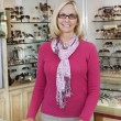 Portrait of a happy senior female optometrist standing in store — Stock Photo